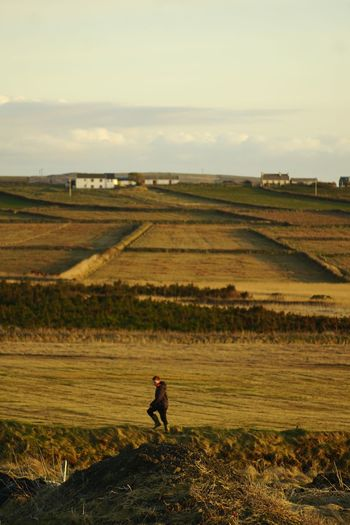 Boy on agricultural field against sky