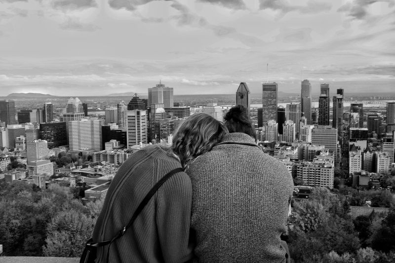 Rear view of couple looking at cityscape against sky