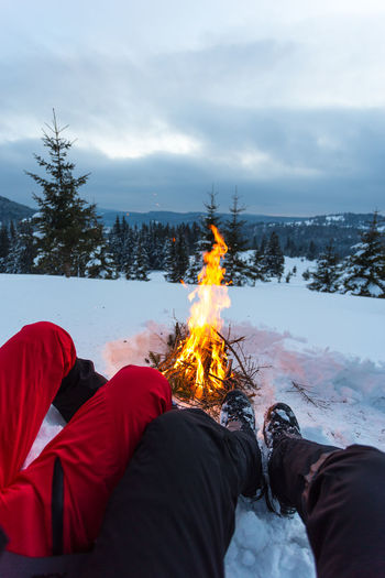 Traveler hiking boots in mountains near bonfire in travel. Trekking boots against fire, travel healthy active lifestyle freedom background. Feet selfie. Man trekking boots relaxing outdoor. Real People Winter Snow Fire - Natural Phenomenon Burning Cold Temperature Fire Nature One Person Tree Flame Sky Leisure Activity Lifestyles Land Plant Unrecognizable Person Bonfire Body Part Outdoors Campfire Bonfire Travel Foot Hiking