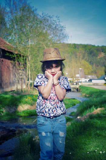 Portrait of cute girl wearing hat standing on grassy field against sky