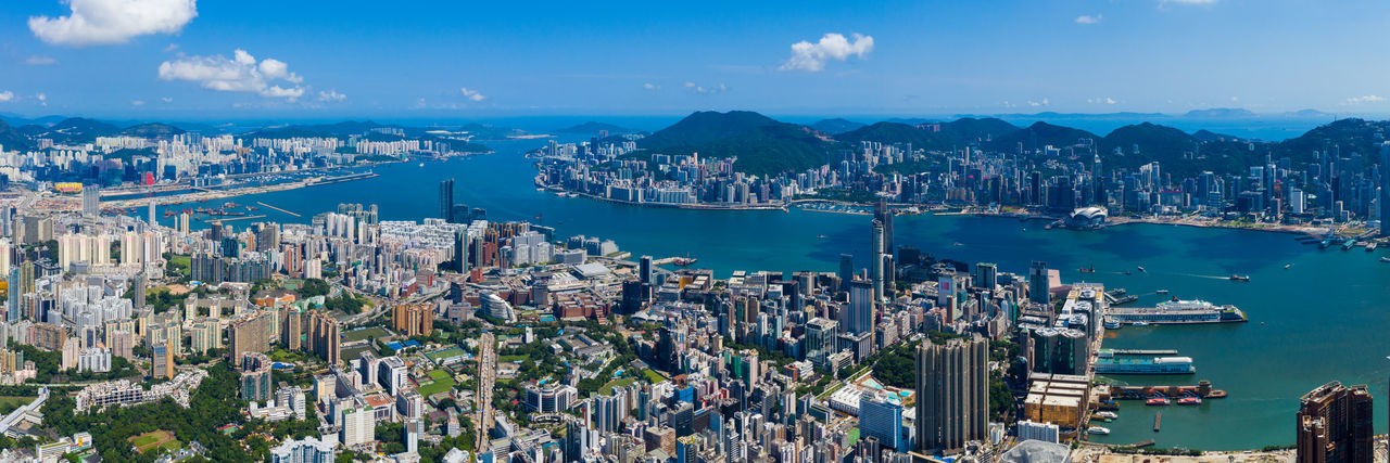 Aerial view of city by bay against sky