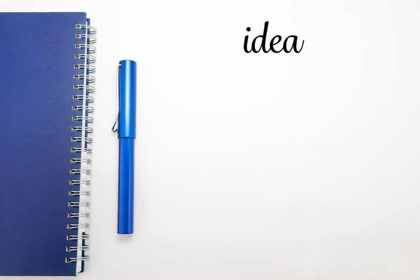 Word idea with notebook and pen in white isolated background Action Plan Blue Checklist Close-up Day Idea Information Information Sign Isolated White Background No People Notebook NotePad Notes Outdoors Pen Stationary White White Background