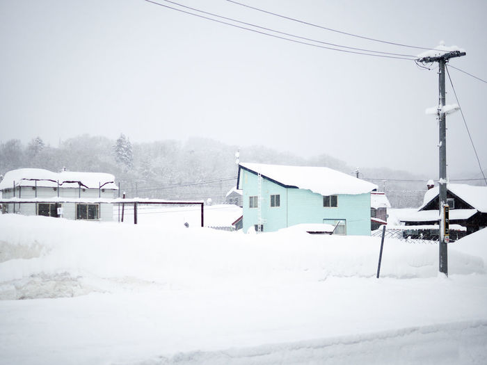Houses on snow covered field by building against sky