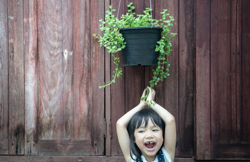 One Person Portrait Leisure Activity Childhood Happiness Wood - Material Real People Child Emotion Looking At Camera Front View Lifestyles Smiling Headshot Plant Innocence Females Cute Fun Outdoors