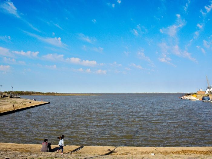 a family enjoy a sunny day at the river Bay Beach Beauty In Nature Calm Cloud - Sky Coastline Day Full Length Men Nature Non-urban Scene Outdoors Person Remote River Scenics Sea Shore Sky Summer Tourism Tranquil Scene Tranquility Vacations Water