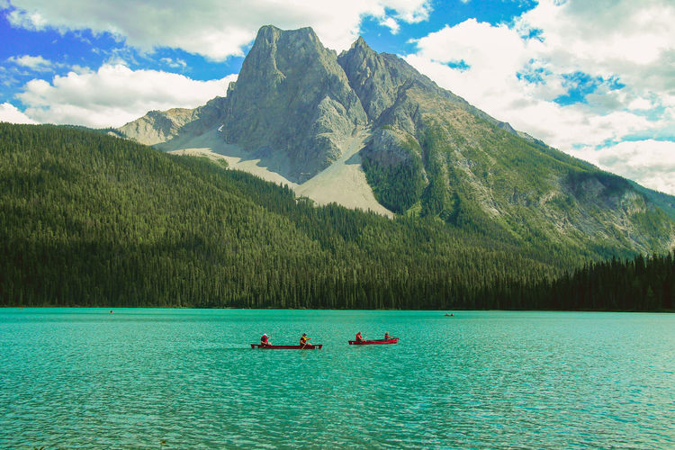 People Rowing Boat Against Grassy Mountain In Emerald Lake At Yoho National Park