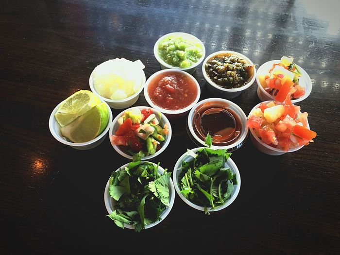 High angle view of taco ingredients in containers on table