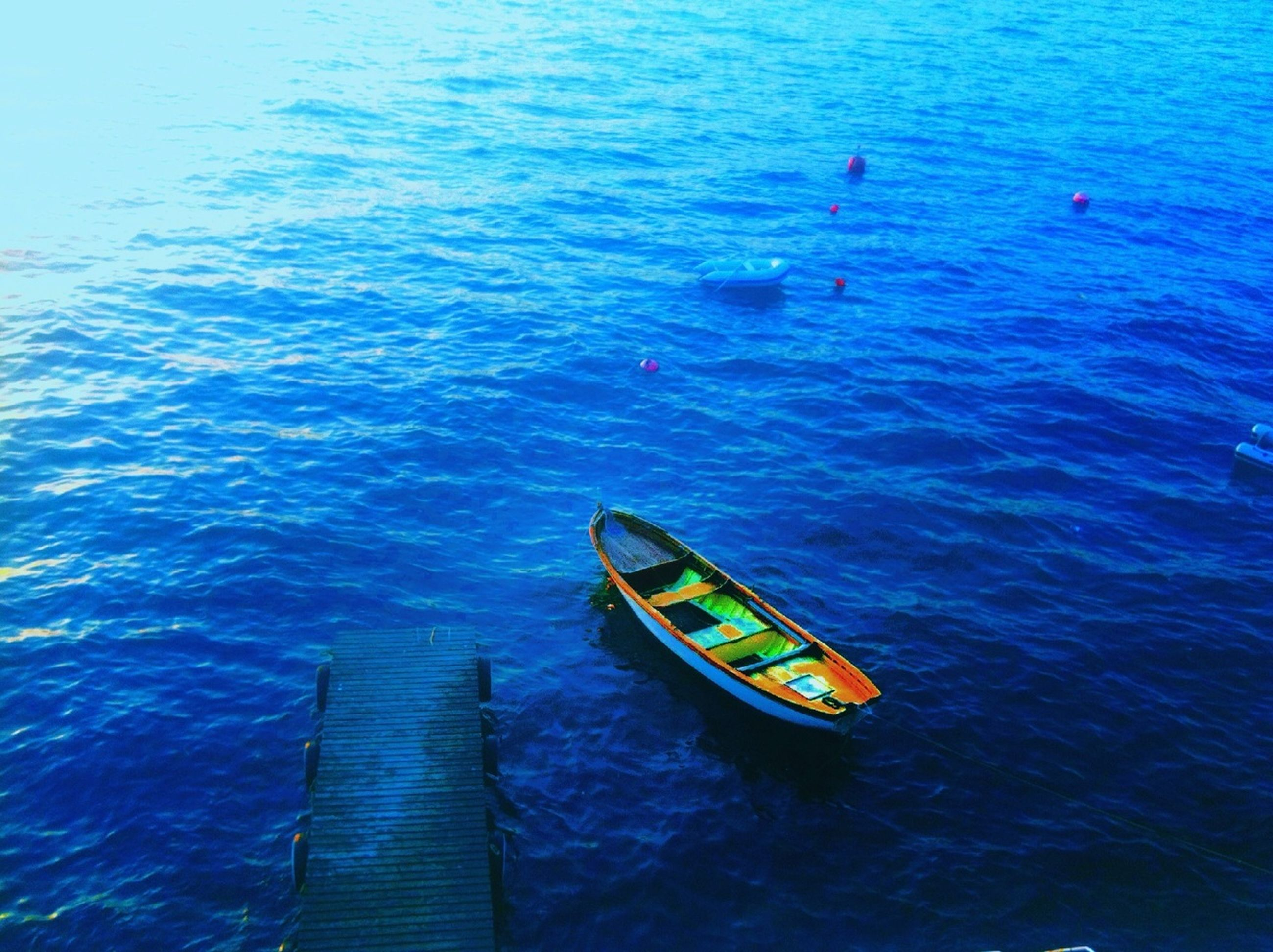 water, blue, nautical vessel, high angle view, transportation, boat, sea, rippled, mode of transport, waterfront, nature, tranquility, turquoise colored, yellow, day, beauty in nature, pier, outdoors, travel, wood - material