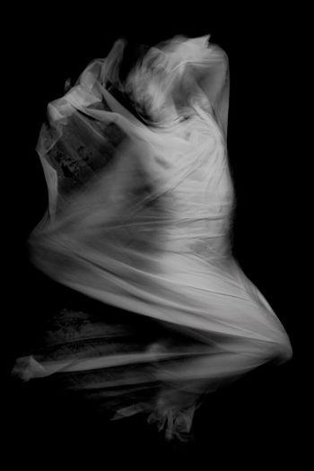 Digital composite image of woman dancing against black background