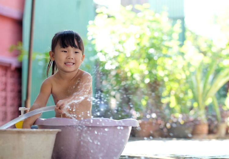 Little girl playing water in the plastic basin happily in the garden. Kids Child Girl Basin Bathtub Bath Water Playing Tub Child Childhood One Person Water Innocence Day Focus On Foreground Lifestyles Nature Looking Three Quarter Length Smiling Happiness Cute Cleaning Real People Outdoors Leisure Activity Hairstyle