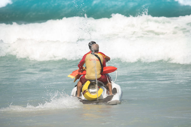 Phuket,Thailand - July 30,2017:Lifeguards on scooter is going out against big wave for tourist rescue. At kata beach in low season ,strong wind from andaman sea and big wave on the beach,lifeguards operating their job to safe tourists . Big Wave Danger Sign Safety First! Scooter Riding  Awareness Beach Dangerous Helping Hand Lifeguard  Rescue Warning