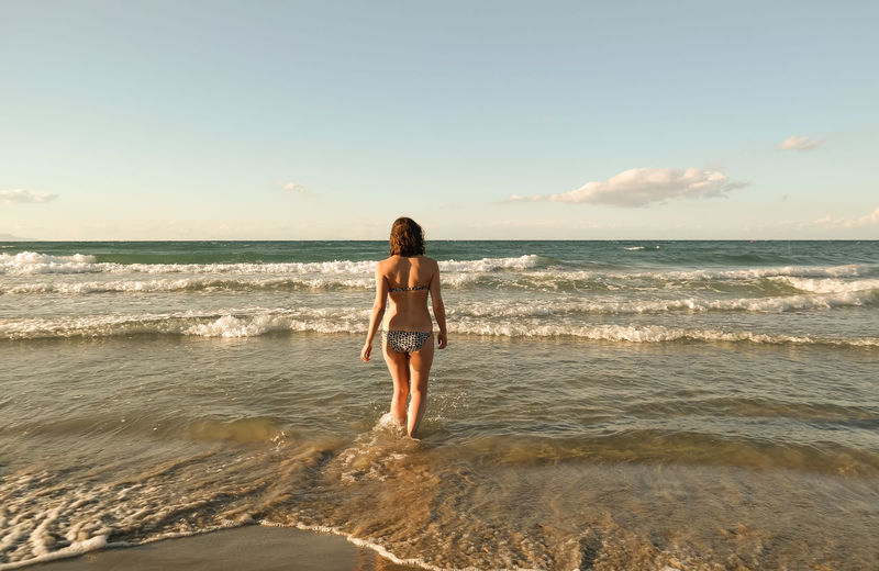 Rear view of young woman in bikini walking at beach against sky