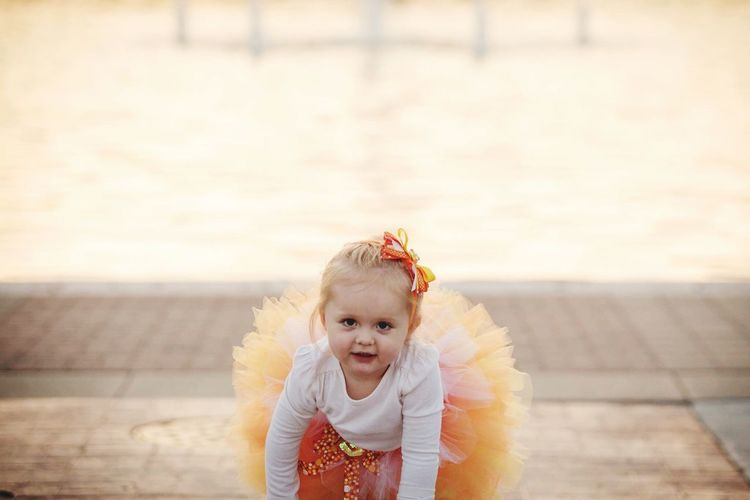 Portrait Of Cute Girl In Tutu Crouching On Footpath