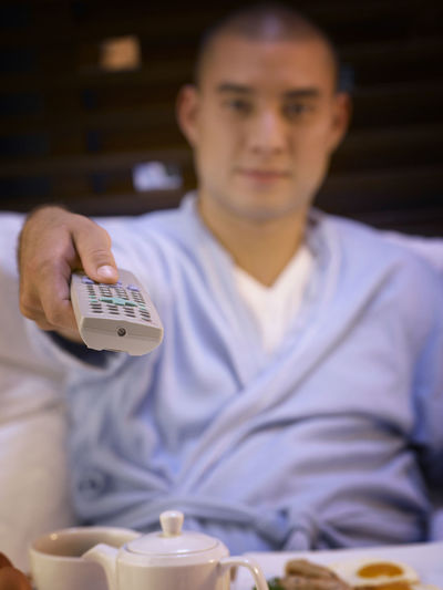 Portrait Of Smiling Man Sitting With Breakfast On Bed While Watching Tv At Hotel