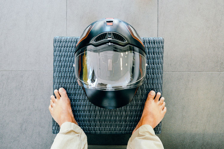 Low section of person standing by helmet