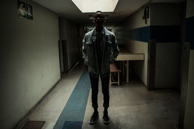 Rear view of person standing in corridor of building