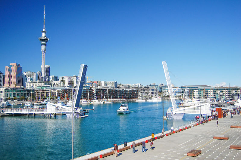 Sailboats in city against clear blue sky