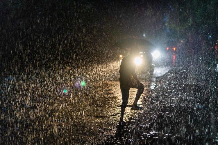 Full length of illuminated street light during rainy season