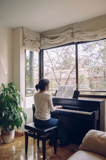 Rear view of woman playing piano at home