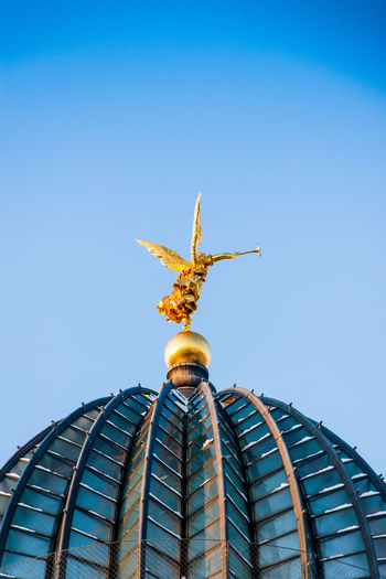 Low Angle View Of Angel Statue On Dresden Frauenkirche Against Sky