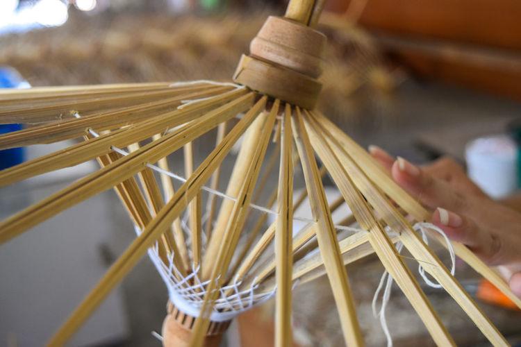 Craftsperson Making Paper Umbrella With Wood At Workshop