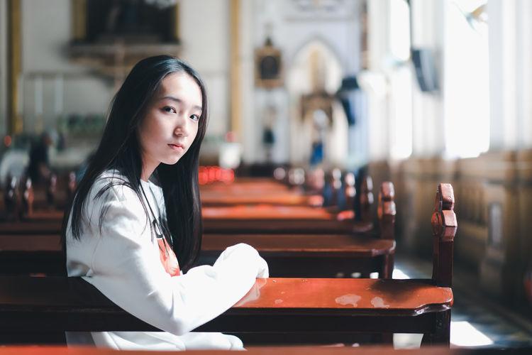 Portrait of teenage girl sitting in church