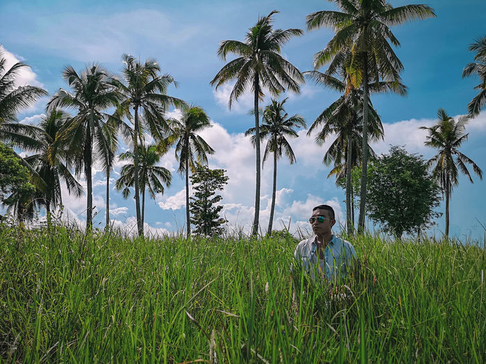 Man In Sunglasses Standing Amidst Grass Against Palm Trees