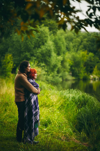 Smiling couple standing by pond over grassy land
