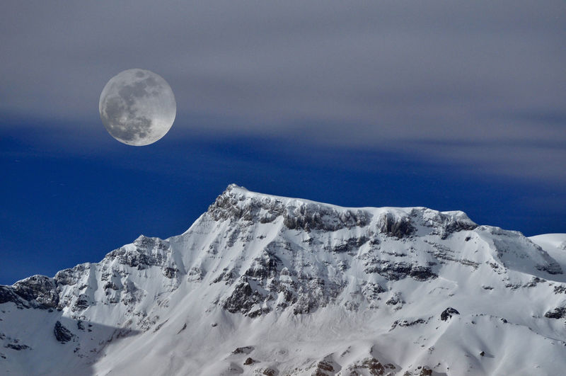 Majestic View Of Full Moon Over Snowcapped Mountain Against Sky At Night