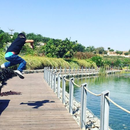 Jump Love Nature Full Length Real People One Person Tree Jumping Clear Sky Day Railing Mid-air Vitality Lifestyles Leisure Activity Outdoors Sky Water Men Nature Stunt