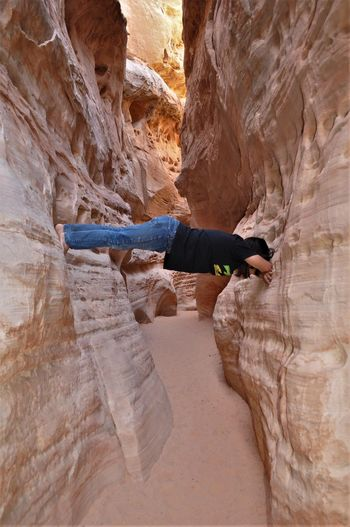 Person Hanging Amidst Rock Formations At Grand Canyon National Park