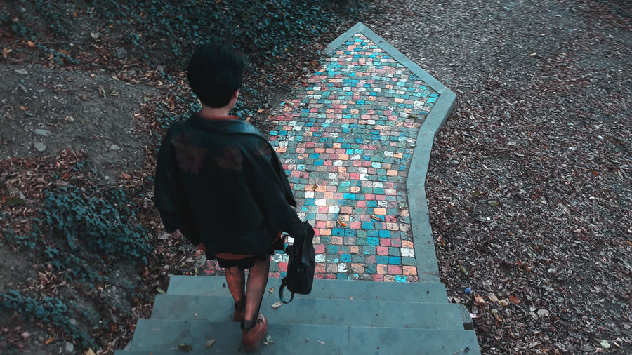 Rear view of woman moving down on steps