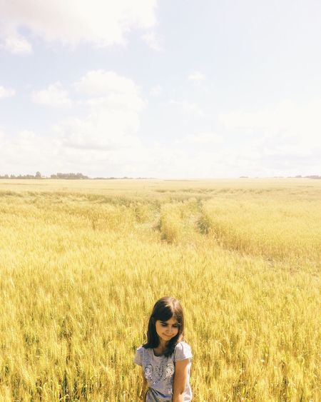 High Angle View Of Woman Standing In Field Against Cloudy Sky On Sunny Day