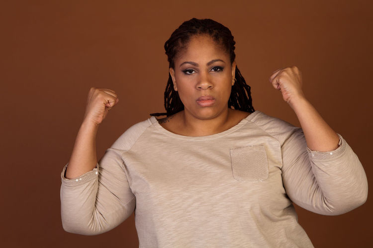 Portrait Of Woman Clenching Fists Against Brown Background