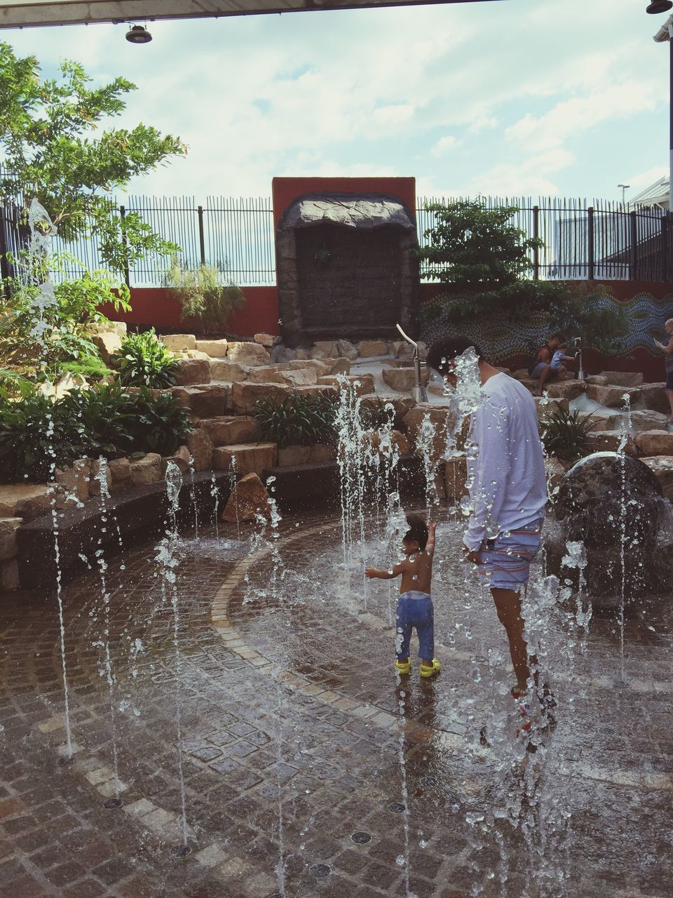 water, childhood, boys, full length, playing, wet, leisure activity, spraying, real people, splashing, standing, fun, togetherness, enjoyment, girls, two people, outdoors, day, motion, bonding, sky, lifestyles, architecture, tree, people