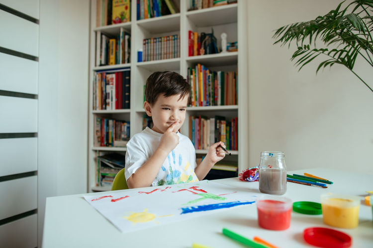 Boy doing painting while sitting at home
