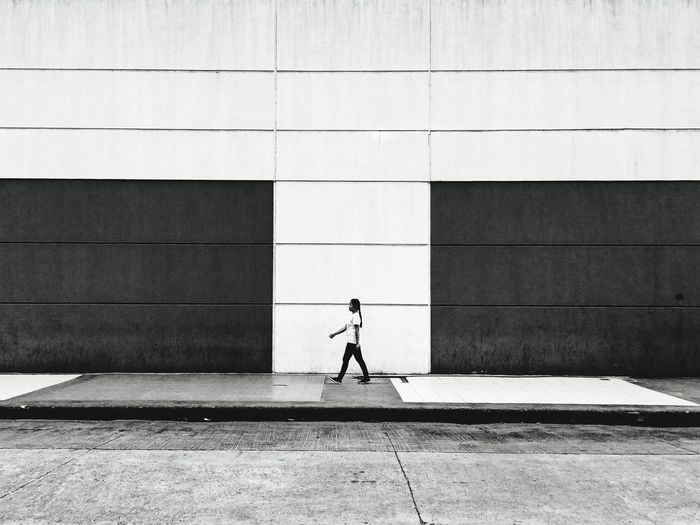 Side view of person walking on footpath against building