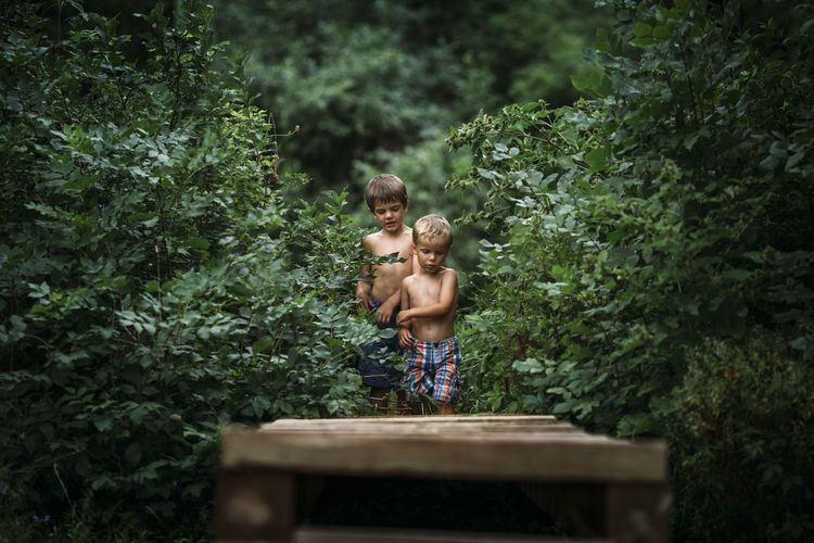 Full length of shirtless boy standing against trees