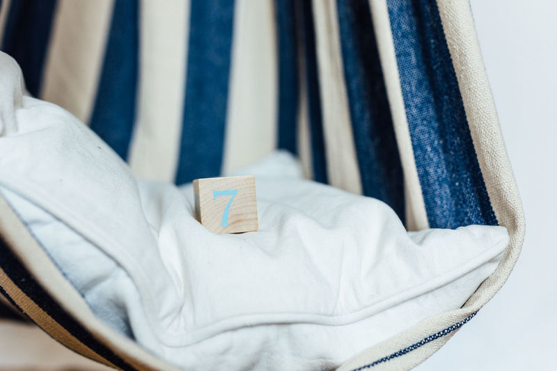 Close-up of wooden block on pillow in white and blue textile