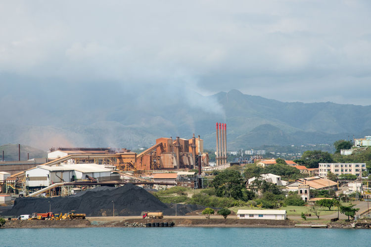 NOUMEA,NEW CALEDONIA-NOVEMBER 25,2016: SLN plant, mountains and Pacific Ocean in Noumea, New Caledonia. Industry Noumea Plant SLN Smoke Smoke Stack Architecture Building Exterior Built Structure Cloud - Sky Energy Environment Environmental Issues Industrica Mountain Mountain Range New Caledonia Nickel Outdoors Pacific Ocean Pollution Sea Sky Water Waterfront