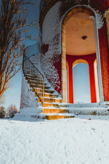 Low angle view of snow on building steps during winter