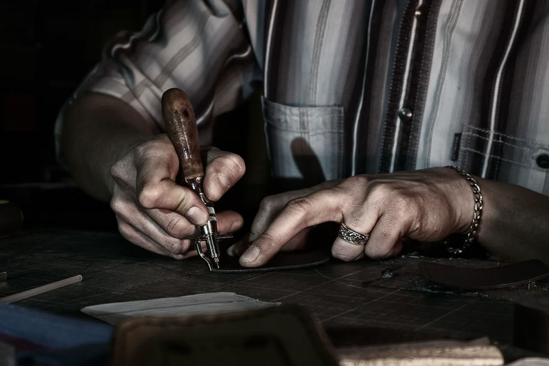 Midsection of man working with leather at table in workshop