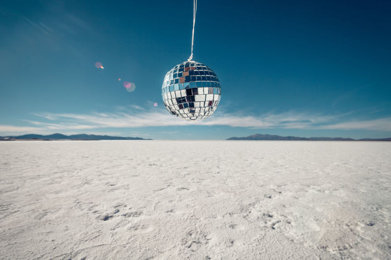 Disco ball over salt flat against blue sky
