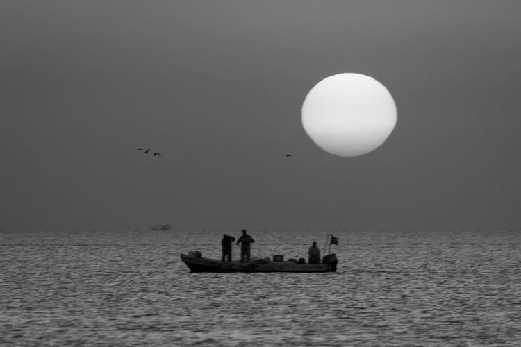 Silhouette Of People On Boat Sailing In Sea During Sunset