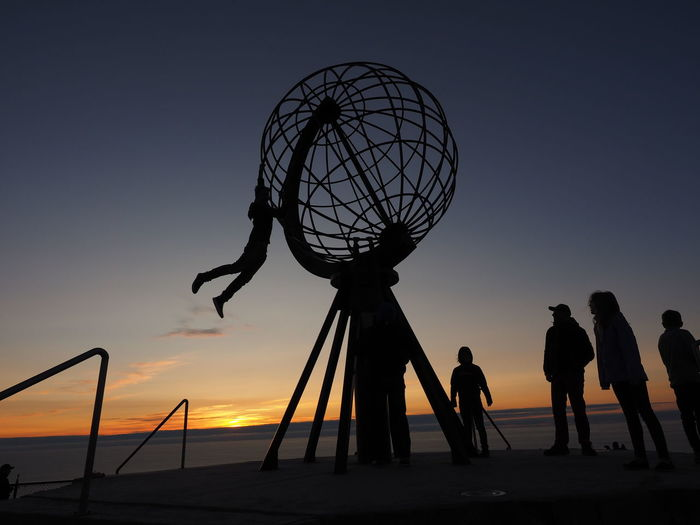 Silhouette people by metallic globe structure against clear sky during sunset