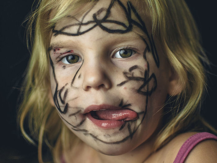 Close-up portrait of messy girl against black background