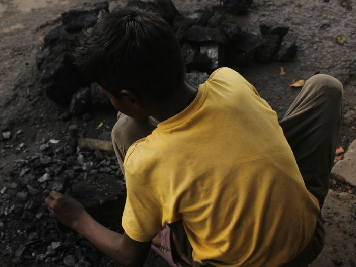 Rear View Of Boy Breaking Coals While Crouching On Rock