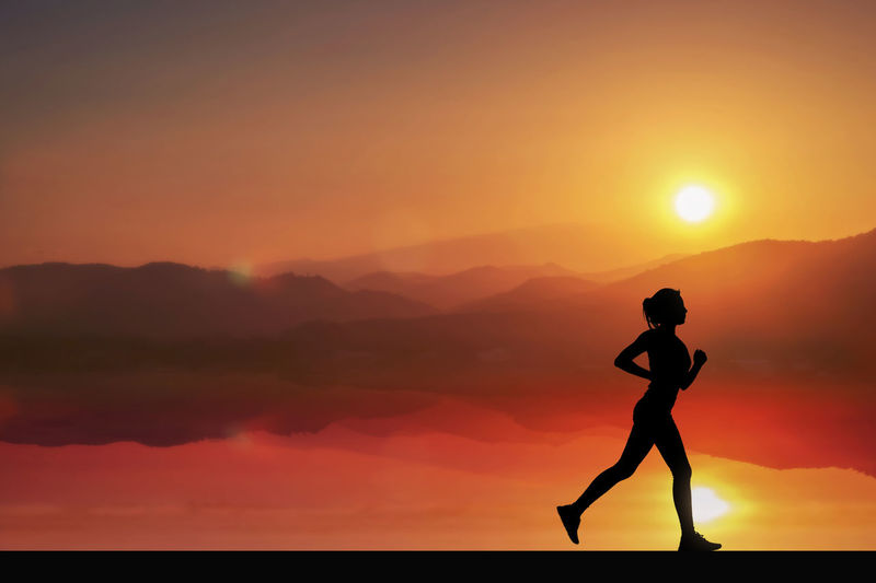 Silhouette woman running against sky during sunset