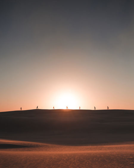 Scenic View Of People On Sand Dune During Sunset