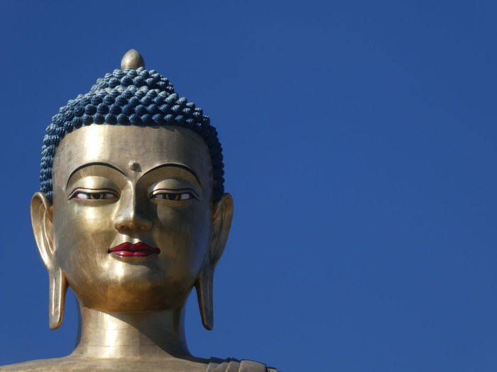 Close-up of buddha statue against clear blue sky
